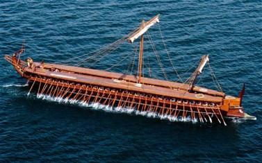 """Το 1987 το Ελληνικό ΠολεμικόΝαυτικό ολοκλήρωσε τη ναυπήγηση και την καθέλκυση ομοιώματος αρχαίας ελληνικής τριήρους με το όνομα """"Ολυμπιάς""""."""