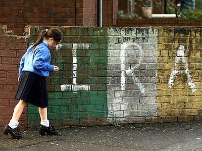 Μικρή μαθήτρια περπατάει μπροστά από έναν τοίχο με γκράφιτι του ΙRA - μια συνηθισμένη εικόνα στο Μπέλφαστ